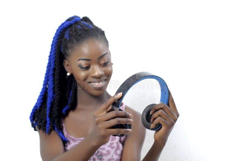Ung afrikansk amerikankvinna som rymmer en headphone royaltyfri fotografi