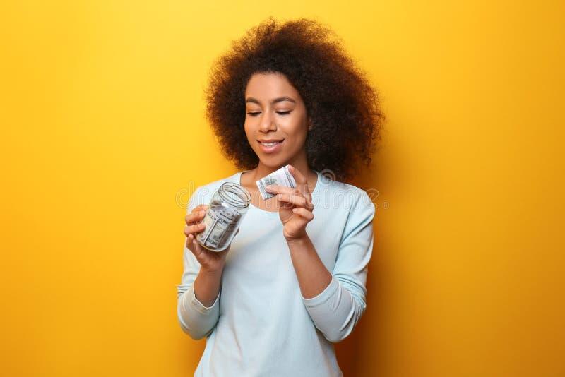 Ung afrikansk amerikankvinna som sätter pengar in i exponeringsglaskruset på färgbakgrund illustration 3d p? vit bakgrund arkivbild