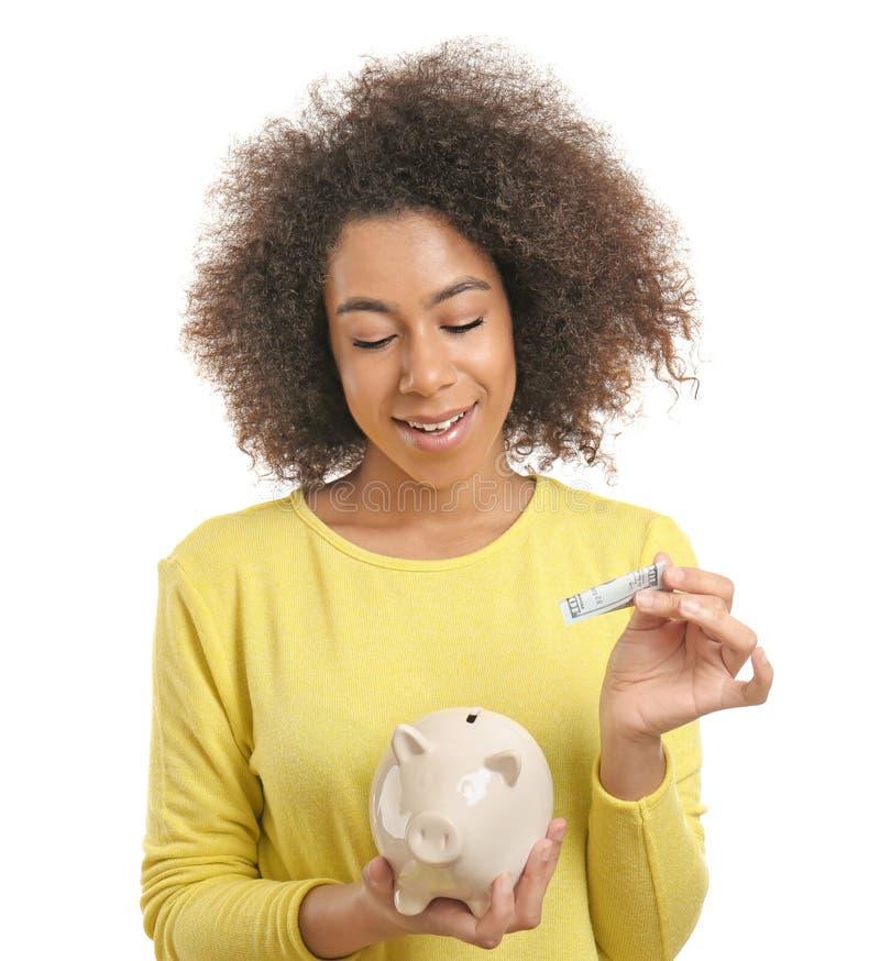 Ung afrikansk amerikankvinna som sätter pengar in i spargrisen på vit bakgrund illustration 3d p? vit bakgrund arkivfoto