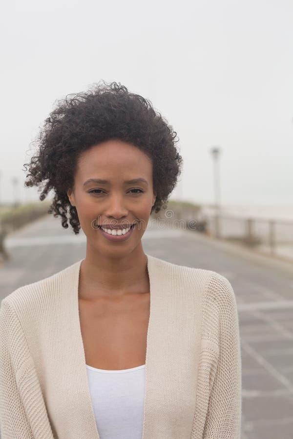 Ung afrikansk amerikankvinna som ser kameran på promenad royaltyfri foto