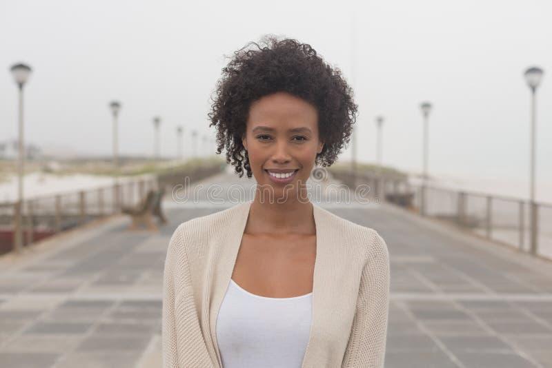 Ung afrikansk amerikankvinna som ser kameran på promenad fotografering för bildbyråer