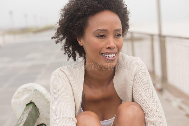 Ung afrikansk amerikankvinna som sitter på bänk på promenad arkivbilder