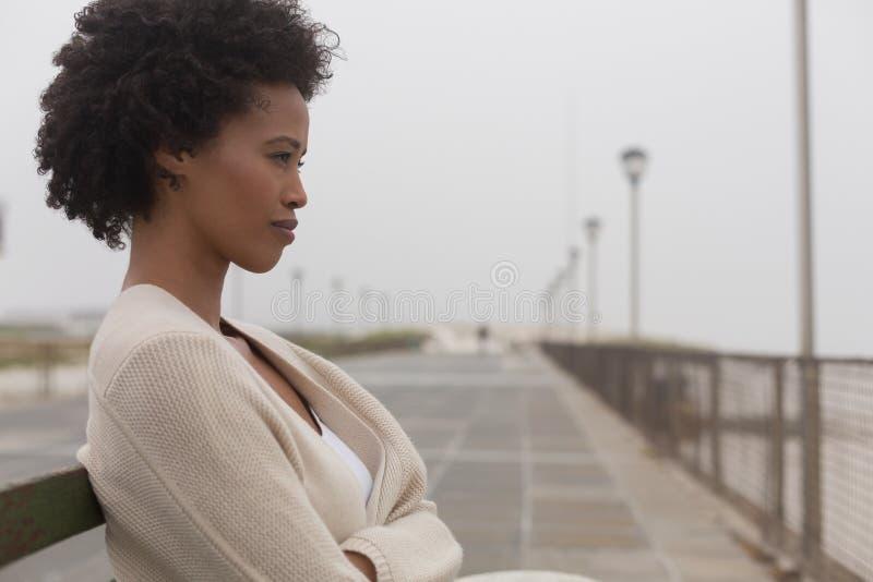 Ung afrikansk amerikankvinna som sitter på bänk på promenad arkivfoton