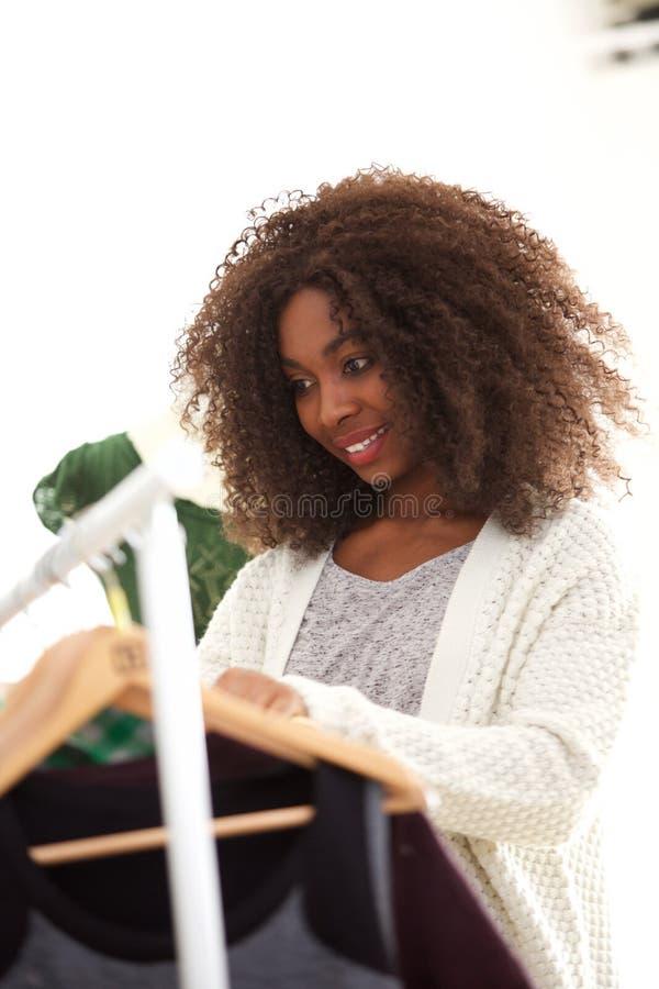 Ung afrikansk amerikankvinnashopping för kläder på lagret som ser klänningarna som hänger på kuggen fotografering för bildbyråer
