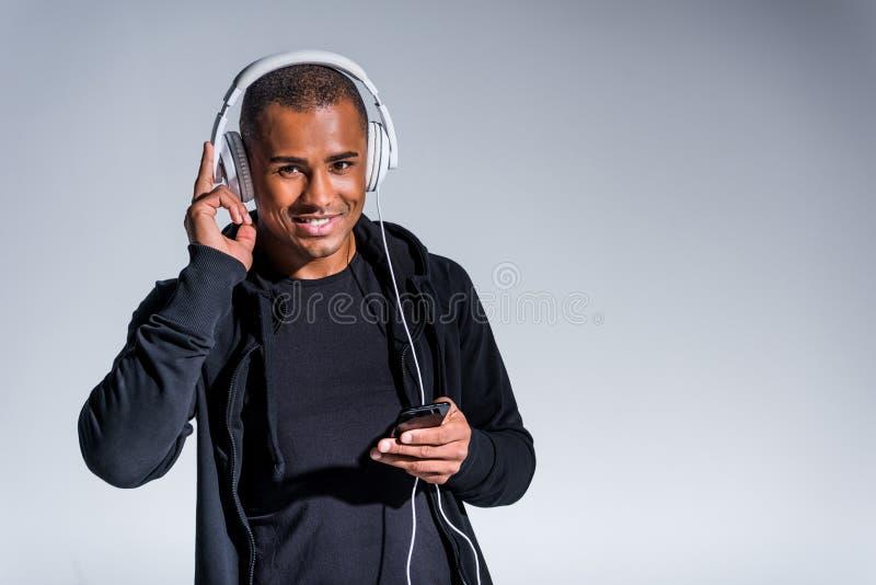 ung afrikansk amerikanman i hörlurar genom att använda smartphonen och le på kameran royaltyfria bilder