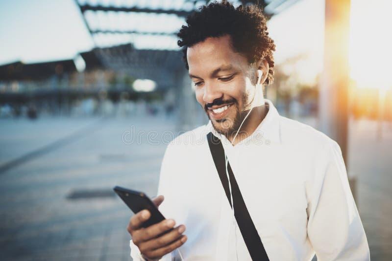Ung afrikansk amerikanman i headphone som går på den soliga staden och tycker om för att lyssna till musik på hans smarta telefon royaltyfri fotografi