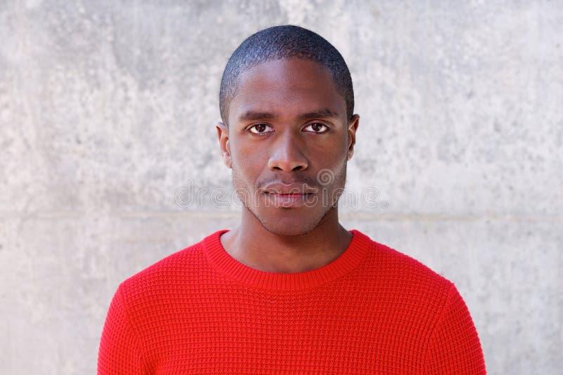 Ung afrikansk amerikanman i rött stirra för tröja royaltyfri fotografi