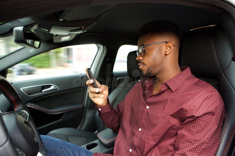 Ung afrikansk amerikanman som ser mobiltelefonen, innan körning i bil arkivbild