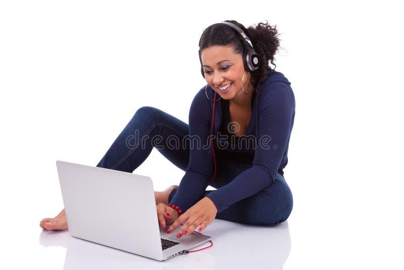 Ung afrikansk deltagareflicka som använder en dator arkivfoton