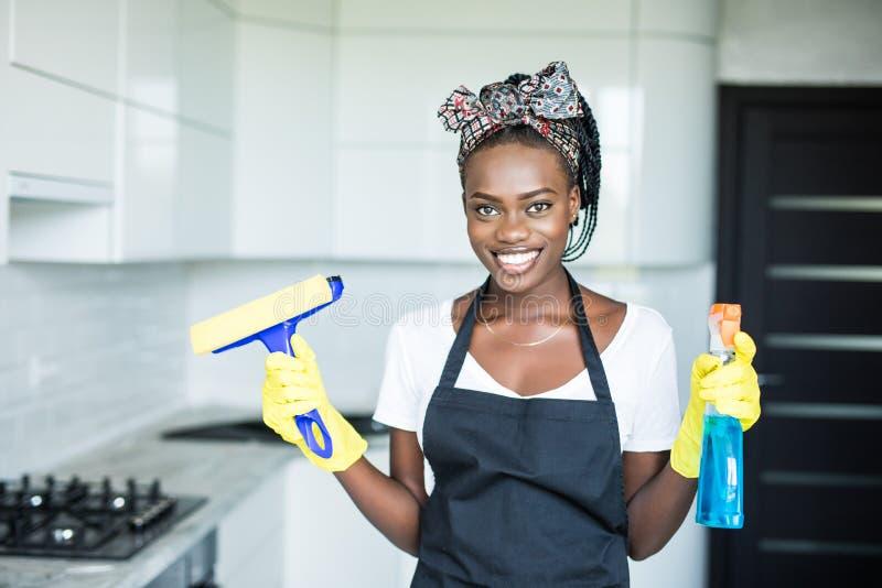 Ung afrikansk kvinna för stående som använder sprej för att torka fönsterexponeringsglas royaltyfri fotografi
