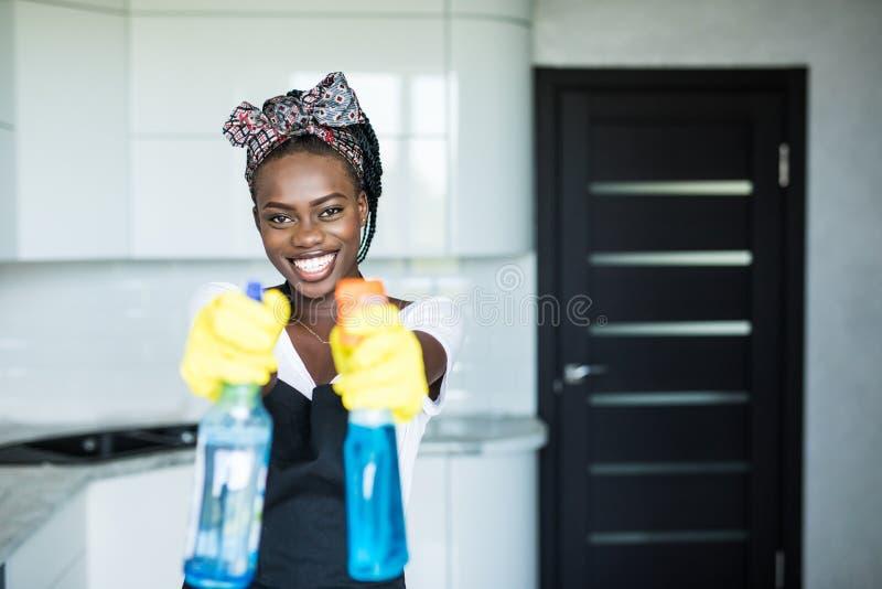 Ung afrikansk kvinna för stående som använder sprej för att torka fönsterexponeringsglas arkivbild