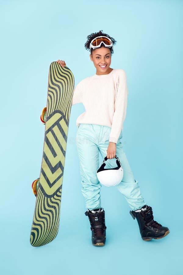 Ung afrikansk kvinna på blått begrepp för snowboarding för sport för väggstudiovinter som utrustas fullständigt arkivfoton