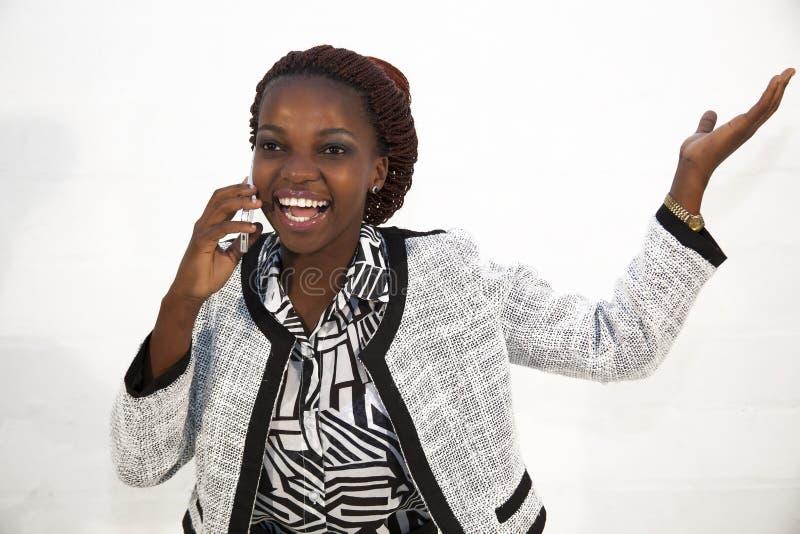 Ung afrikansk kvinna på mobiltelefonen fotografering för bildbyråer