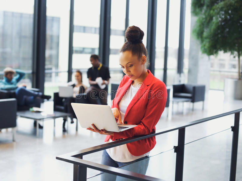 Ung afrikansk kvinna som i regeringsställning använder bärbara datorn arkivbild