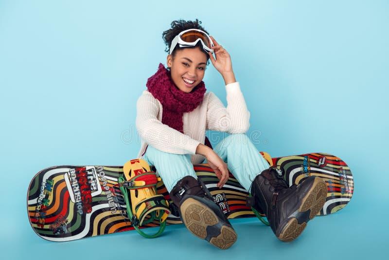 Ung afrikansk kvinna som isoleras på blått sammanträde för begrepp för snowboarding för sport för väggstudiovinter med brädet royaltyfri fotografi