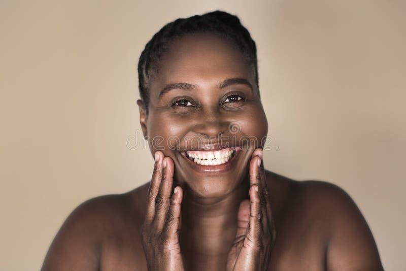 Ung afrikansk kvinna som ler och trycker på hennes perfekta hy royaltyfri foto