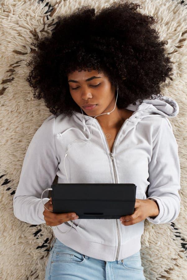 Ung afrikansk kvinna som ligger på golv och använder den digitala minnestavlan royaltyfria bilder
