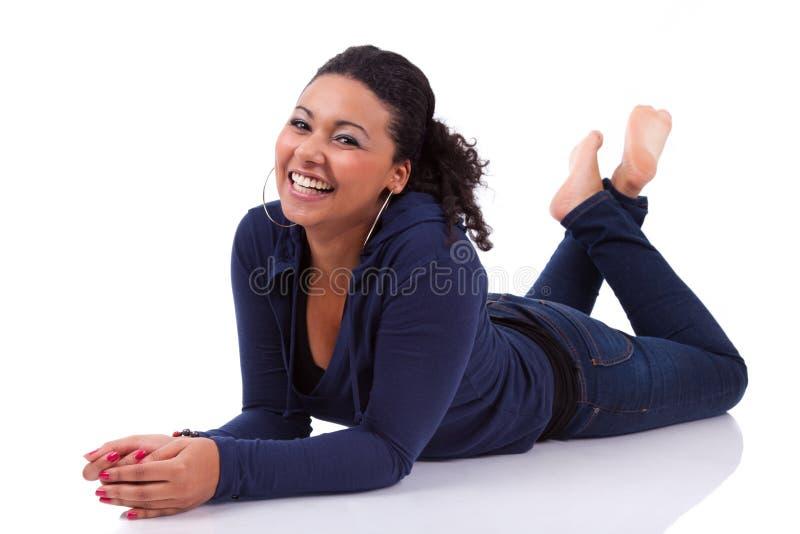Ung afrikansk kvinna som ner ligger på golvet arkivbilder