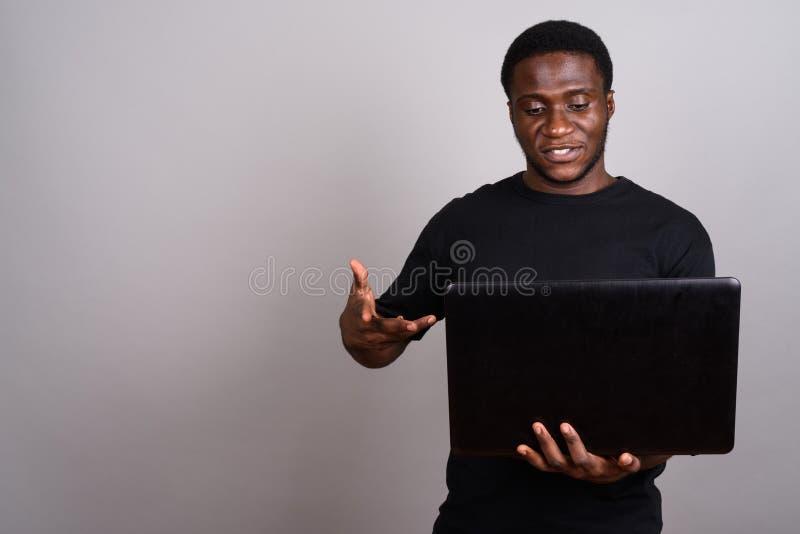 Ung afrikansk man som bär den svarta skjortan mot grå bakgrund royaltyfri fotografi