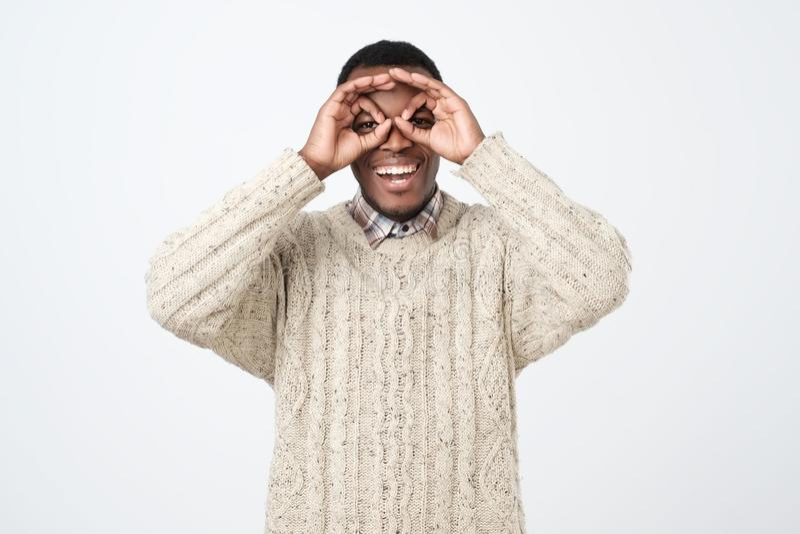 ung afrikansk man som ler och gör kikare med hans händer som bär tröjan royaltyfria foton