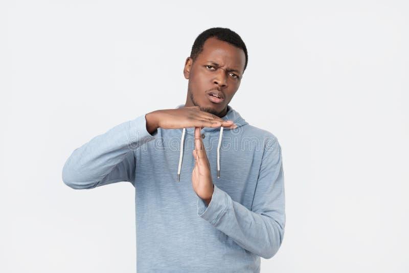 Ung afrikansk man som ut visar handgest för tid fotografering för bildbyråer