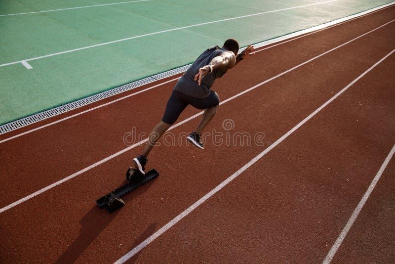 Ung afrikansk manlig löparespring på löparbana royaltyfri bild