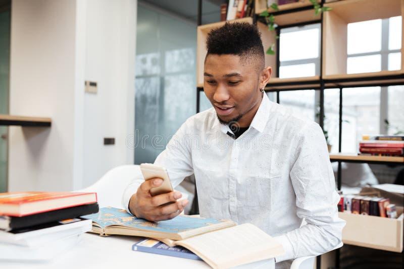 Ung afrikansk student i arkiv som pratar vid hans telefon arkivbilder
