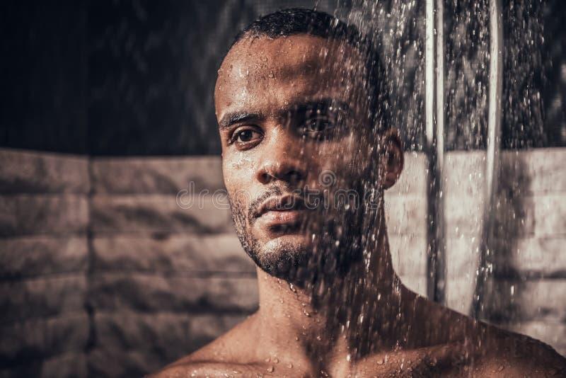 Ung Afro--amerikan man som tar duschen i badrum arkivbild
