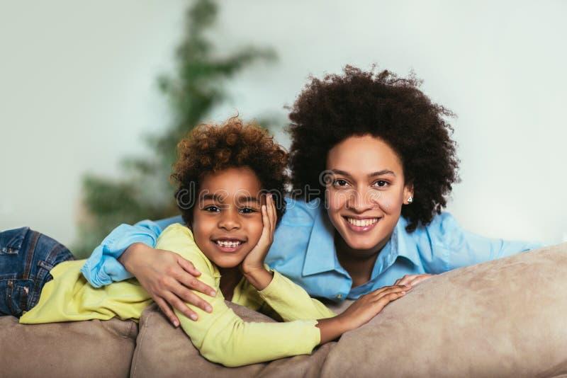 Ung afro--amerikan moder med den gulliga lilla dottern royaltyfri foto