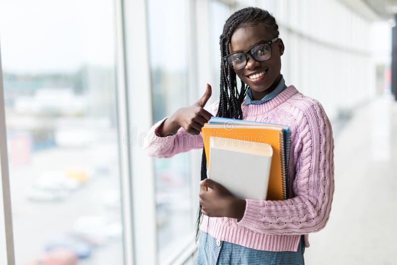 Ung afro amerikansk studentkvinna som rymmer anteckningsböcker och showtummar upp gest nära panorama- fönster i modernt universit royaltyfri bild