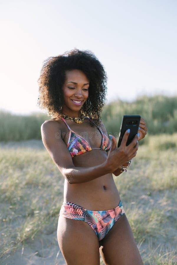 Ung afro h?rkvinna som tar selfie p? stranden arkivfoton