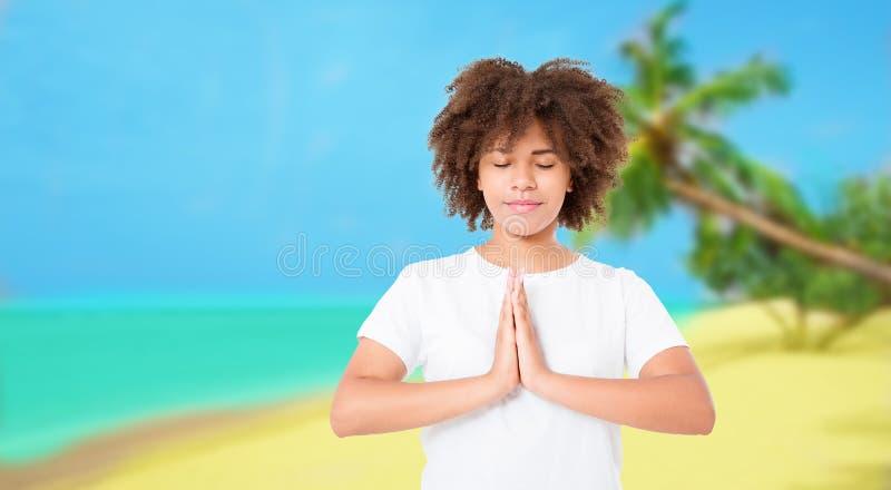 Ung afro kvinna som mediterar på stranden med stängda ögon Yogaasanaen med ögon stängde sig Kvinna under meditation med namastehä arkivbilder