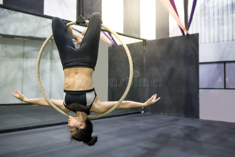 Ung akrobatisk kvinna som hänger på flyg- beslag royaltyfria bilder