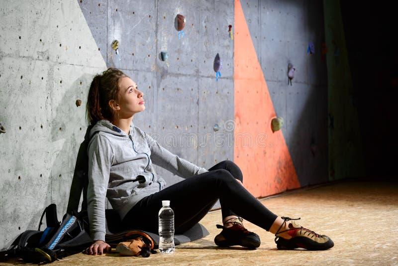 Ung aktiv kvinna som vilar, efter Bouldering på konstgjort har vaggat, i att klättra idrottshall Extrem sport och inomhus klättri royaltyfria foton