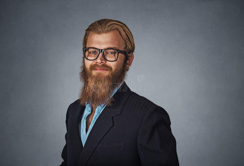 Ung allvarlig affärsman i exponeringsglas som ser raka på att le för kamera royaltyfri foto