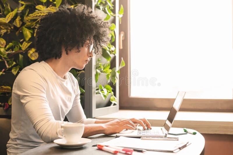 Ung allvarlig man som arbetar i kafét som skriver artikeln på bärbara datorn royaltyfri bild