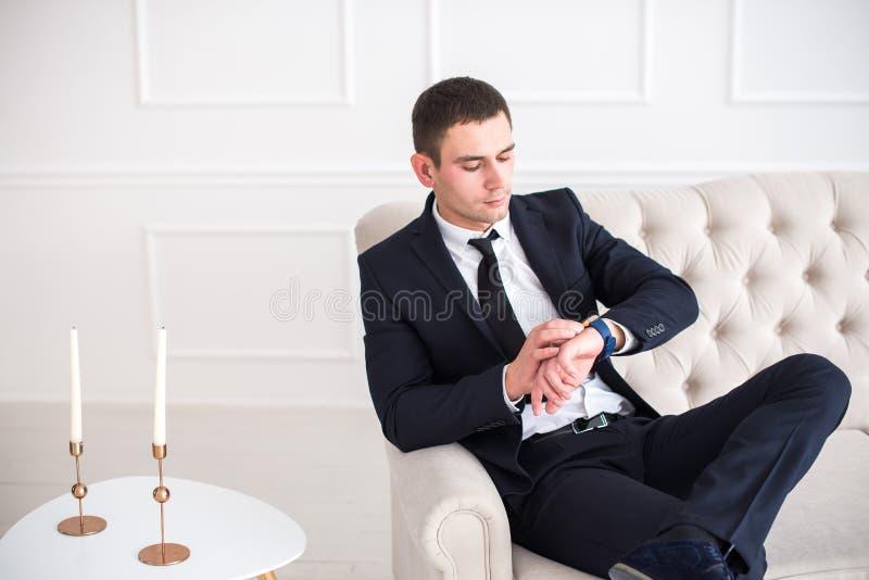 Ung allvarlig och säker man, i sammanträde för affärsdräkt på soffan och att se klockan arkivbilder