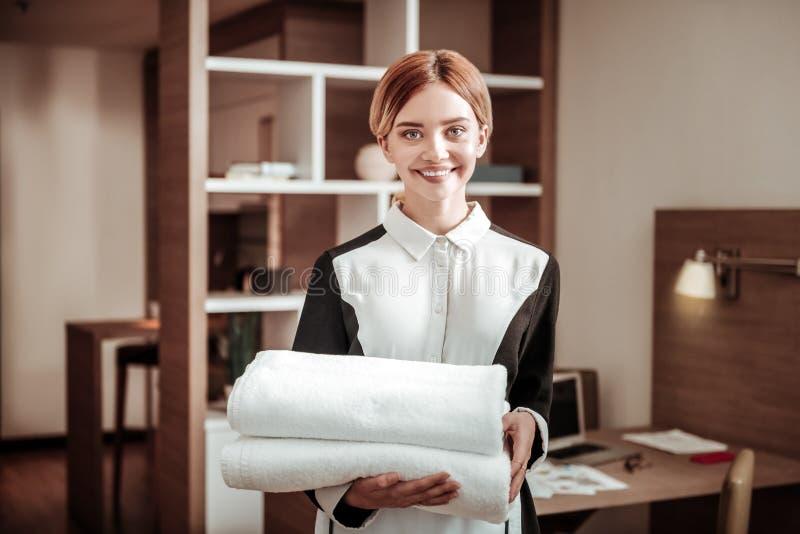 Ung angenäm blondin-haired hotellhembiträde som rymmer vita handdukar arkivbilder