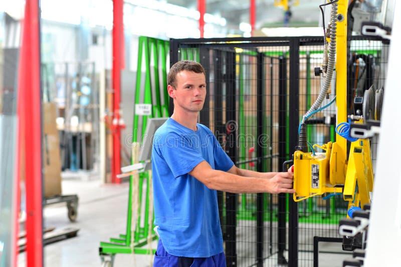 Ung anställd i ett exponeringsglas för företagstillverkningssäkerhet för husbyggnationer med ett lyftande hjälpmedel arkivbild