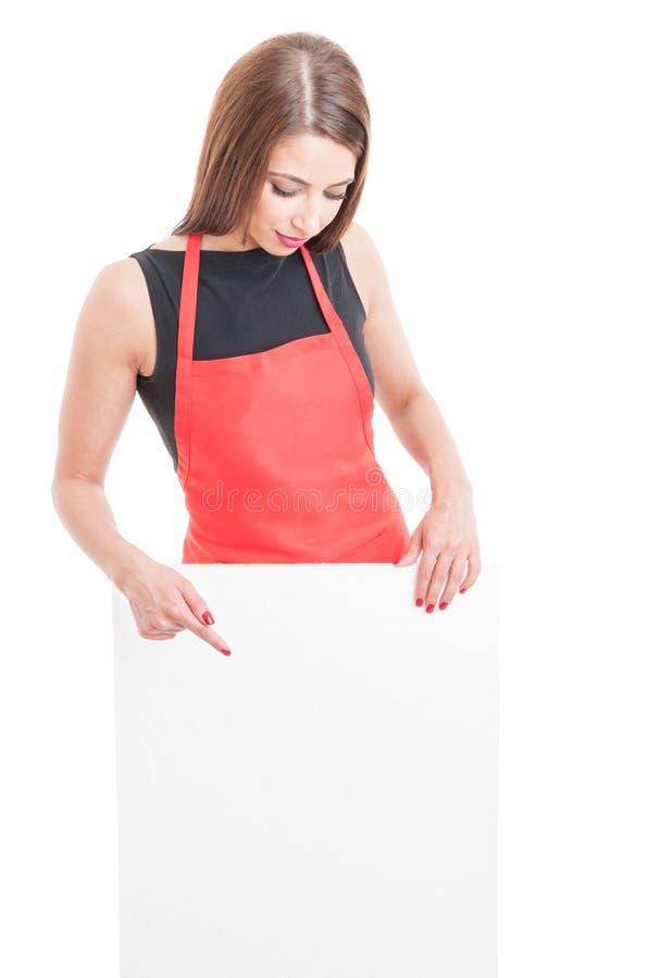 Ung anställd med förklädet som pekar på papp arkivfoto