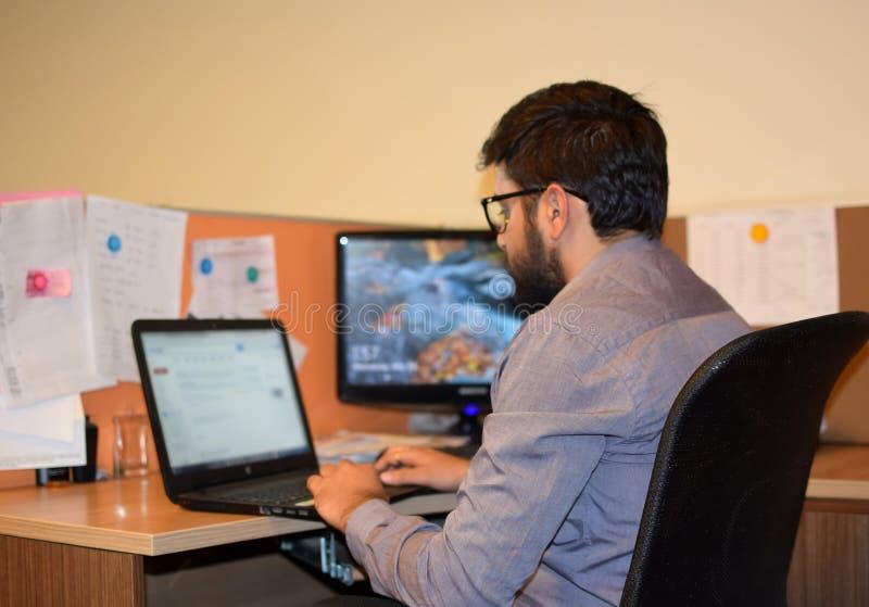 Ung anställd som i regeringsställning arbetar på bärbara datorn under kontorsarbetstid royaltyfri foto