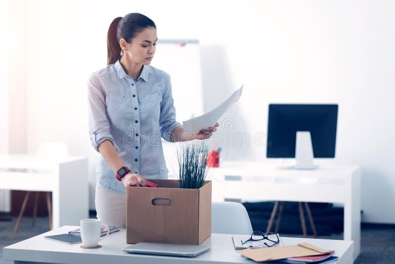Ung anställd som packar hennes material i ask, medan lämna arbete arkivfoton