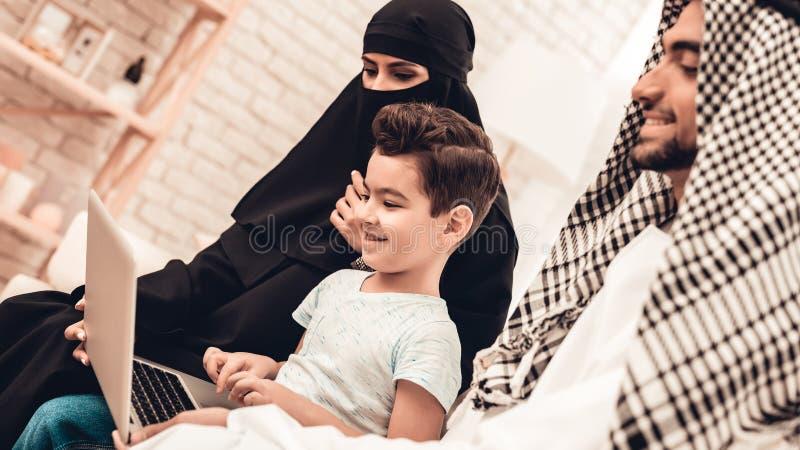 Ung arabisk familj som hemma använder bärbara datorn på soffan royaltyfri fotografi