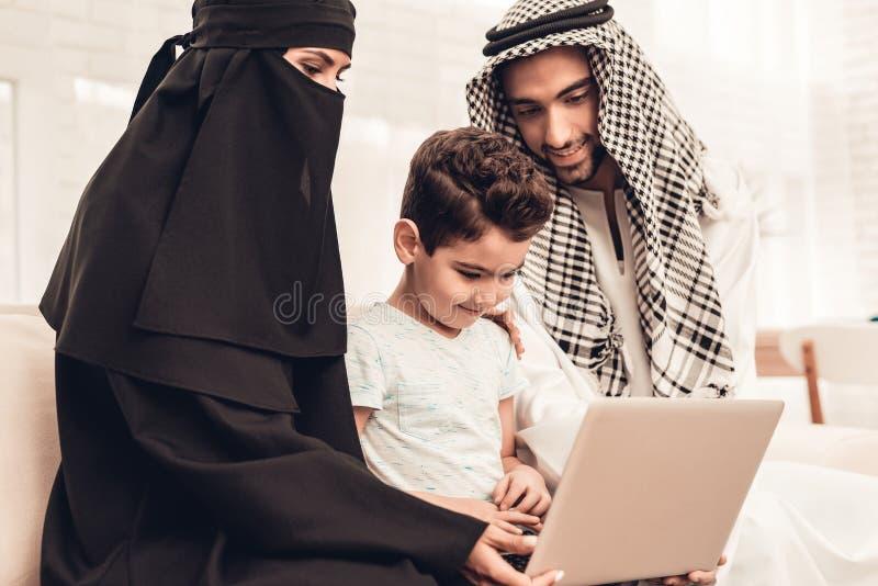 Ung arabisk familj som hemma använder bärbara datorn på soffan arkivfoto