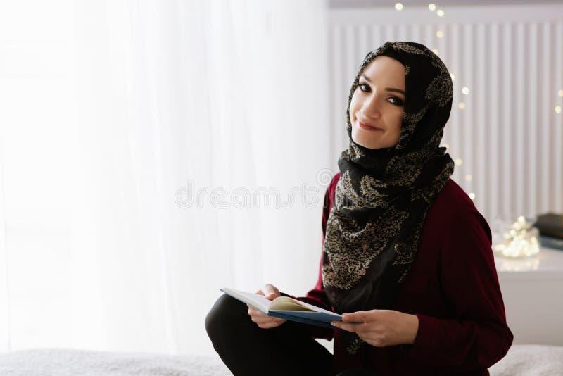 Ung arabisk kvinna i hijab som läser en bok royaltyfria bilder