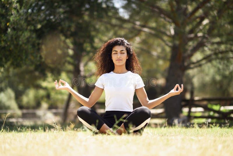 Ung arabisk kvinna som gör yoga i natur arkivbild
