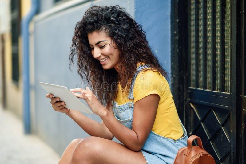Ung arabisk kvinna som utomhus använder hennes digitala minnestavla arkivbild