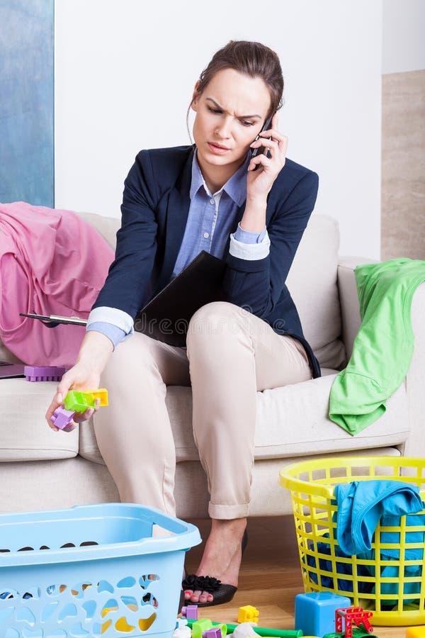 Ung arbetande mamma som talar på telefonen royaltyfri bild