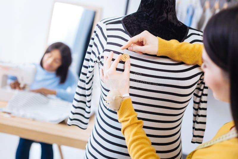 Ung arbetare av en atelier som tillfogar en trevlig knapp till en blus royaltyfria foton