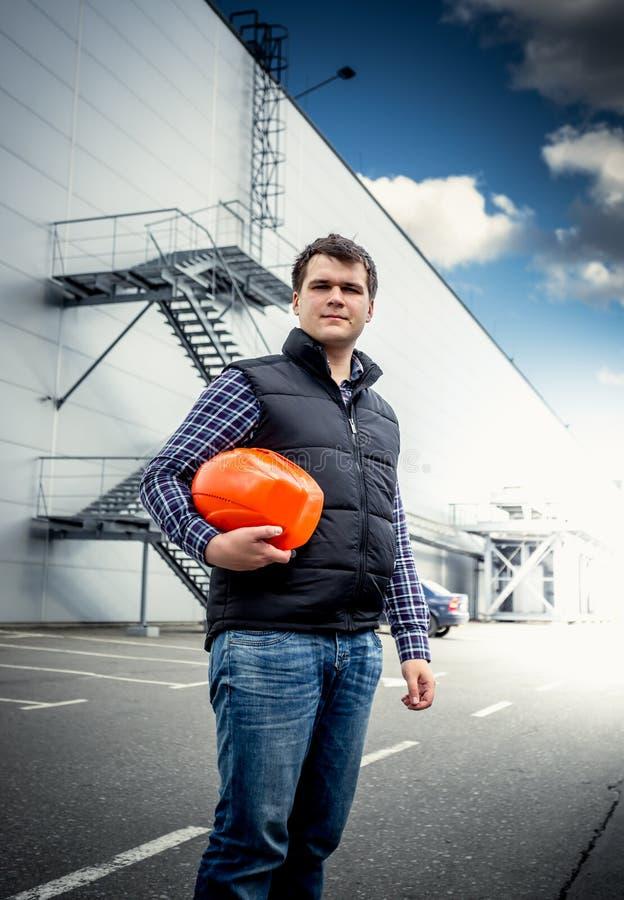 Ung arkitekt som poserar med hardhaten mot industribyggnad fotografering för bildbyråer